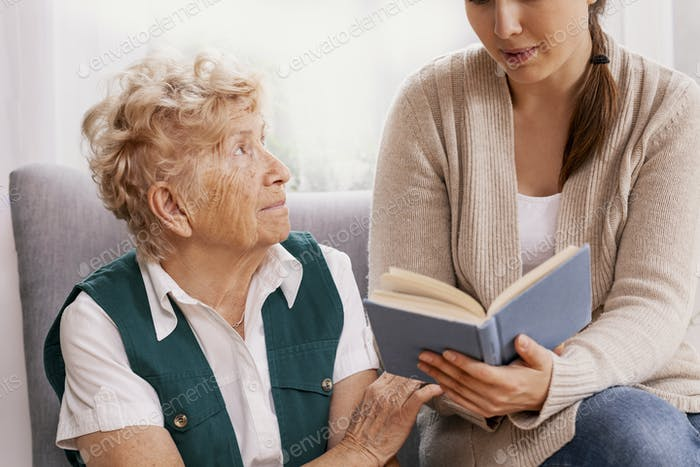 Grandmother and granddaughter spend time together reviewing the photo album