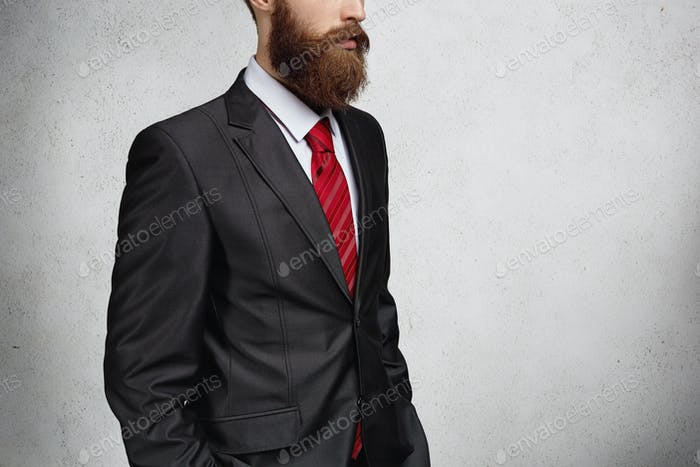 Business, success and achievement concept. Handsome young employee with stylish beard, dressed in el