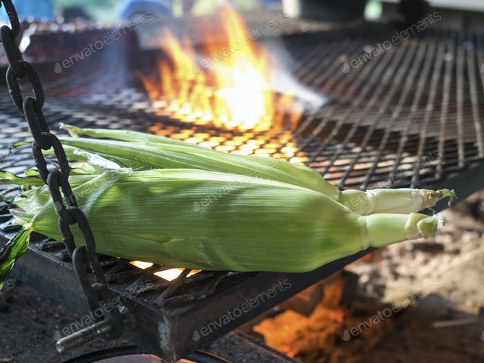 Sweetcorn roasting on a barbeque outdoors.