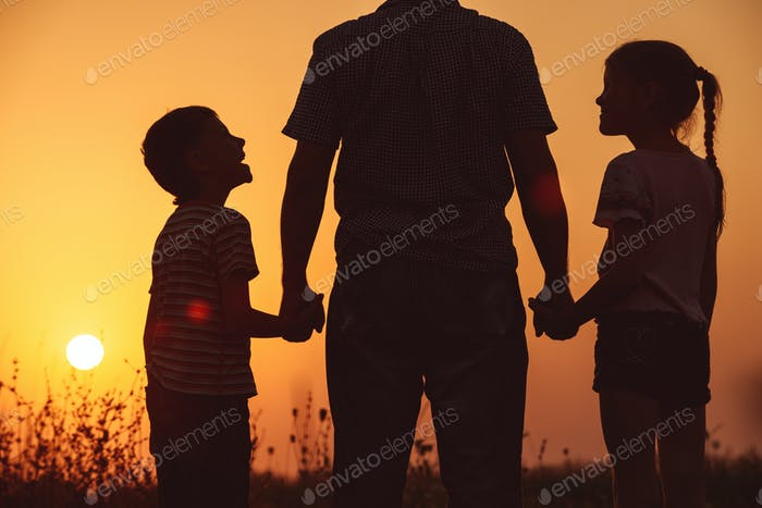 Father and children standing in the park at the sunset time.