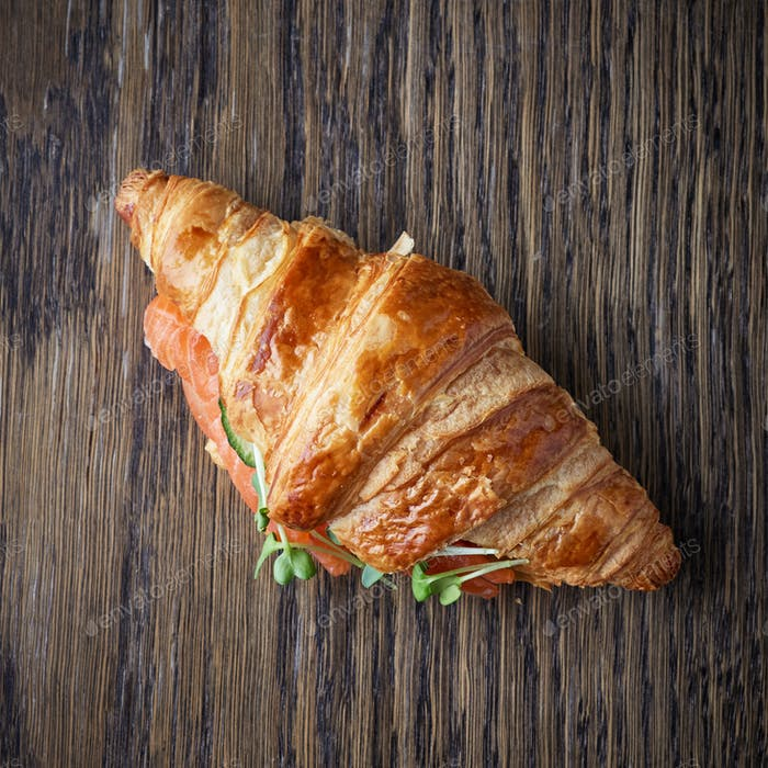 Fresh croissant with salmon and greens