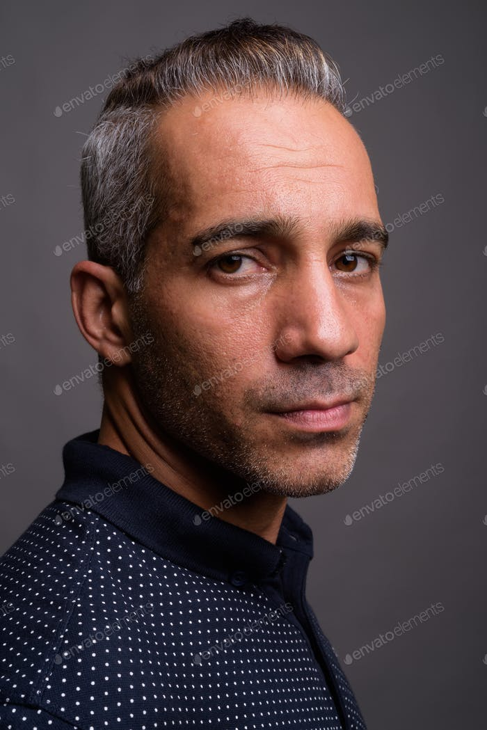 Face of handsome Persian man with gray hair against gray background