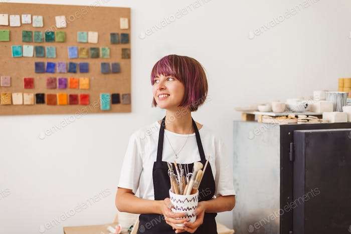 Girl with colorful hair in black apron and white T-shirt holding mug with pottery tools in hands