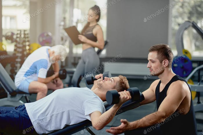 Personal coach helping guy doing exercises lying with dumbbells in gym
