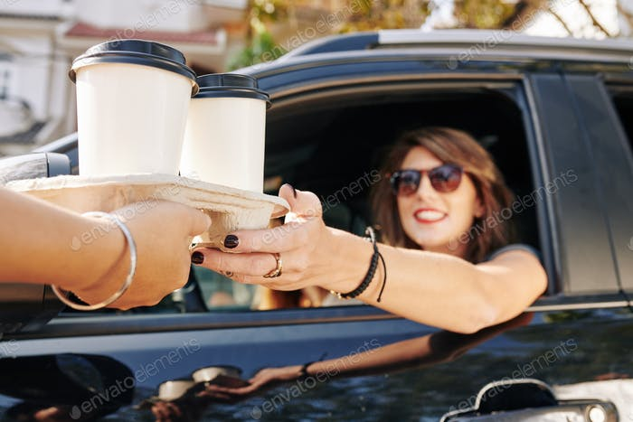 Waiter giving coffee cups to female driver