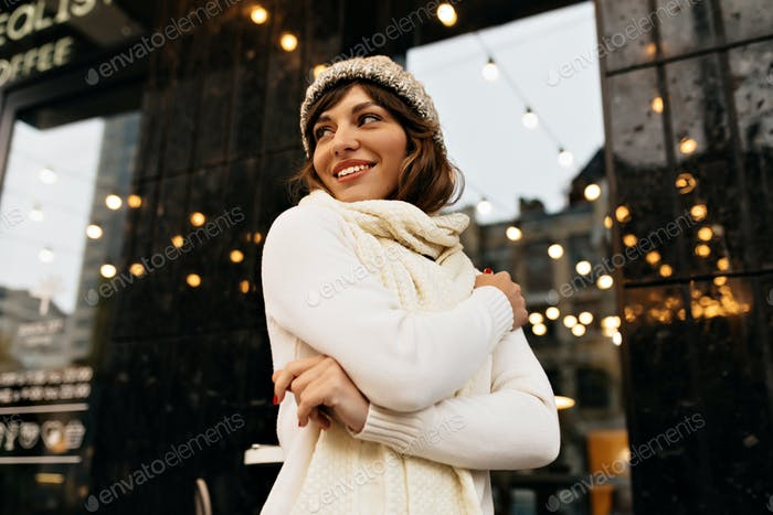 Happy lovable woman in white winter outfit walking on the street with happy smile