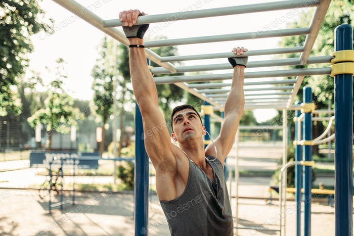Male athlete training on horizontal bars outdoor