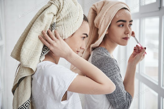 Sisters have skincare using brush with powder. With towels on the heads