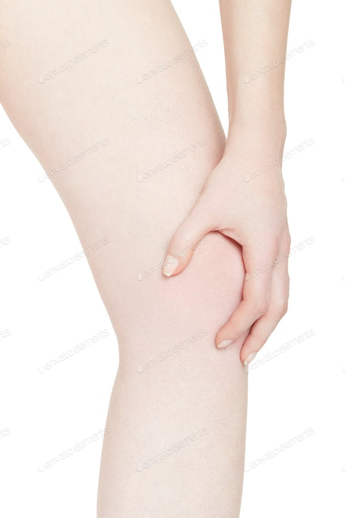 Young woman holds her hand on knee, pain isolated on white