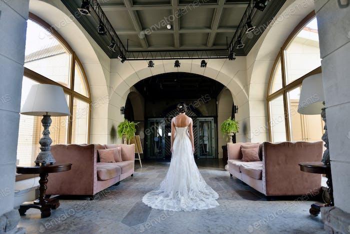 Beauty Braut in Spitze Brautkleid drinnen