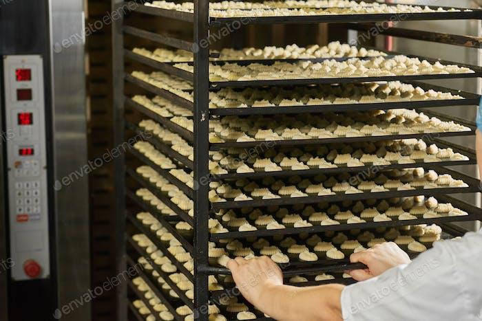 Creame cakes from raw dough on shelfs