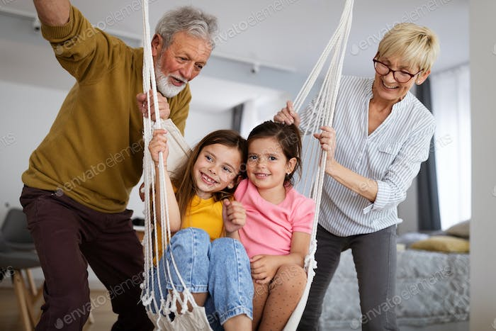 Portrait of happy elderly couple and grandchildren playing together