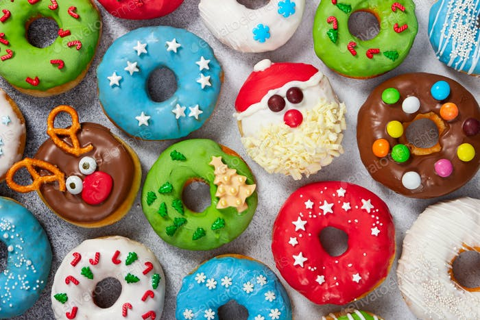 Set of Christmas donuts on gray stone background.