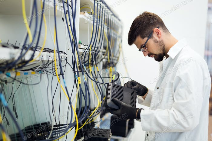 Picture of network technician testing modems in factory