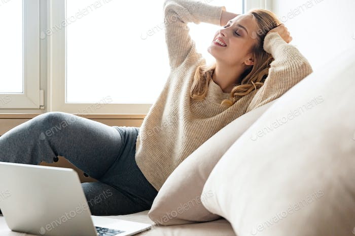 Optimistic young woman using laptop computer.