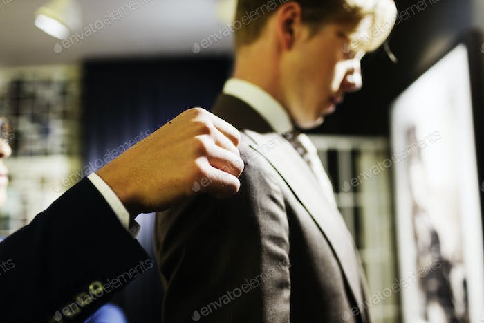 Sales clerk adjusting customer's suit in fitting room at clothing store