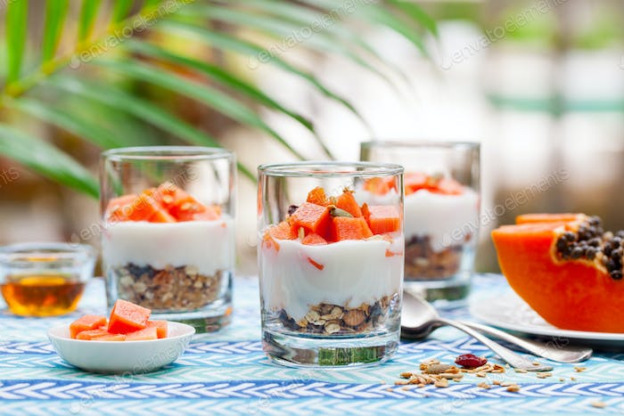 Dessert with Papaya, Yogurt and Granola in Glasses. Outdoor Background.