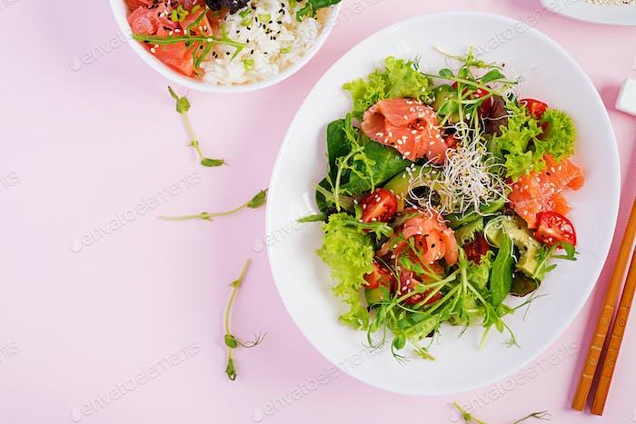 Buddha bowl with rice, mango, avocado and salmon and fresh salad