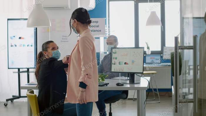 Businesswoman touching elbow for respecting social distancing