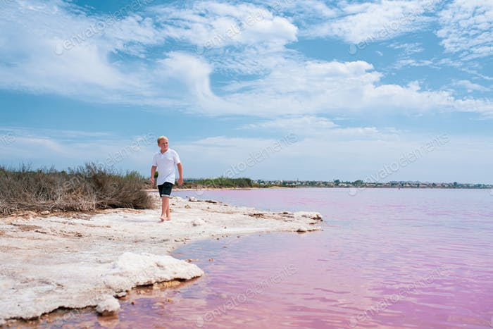 cute teenager boy wearing summer clothes walking on pink lake