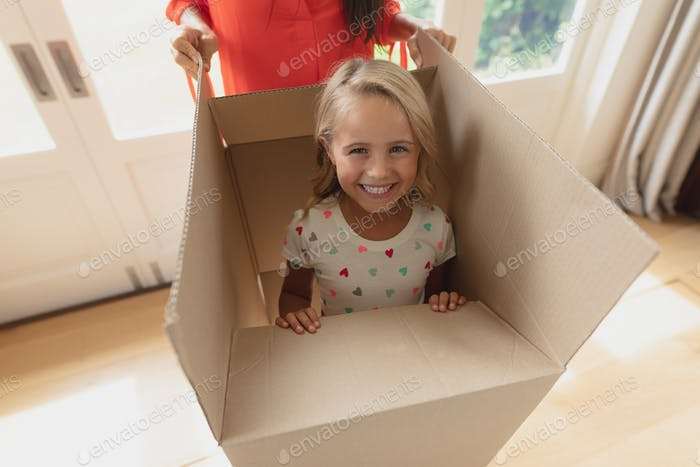 Front view of Caucasian mother and daughter playing with cardboard box in living room at home