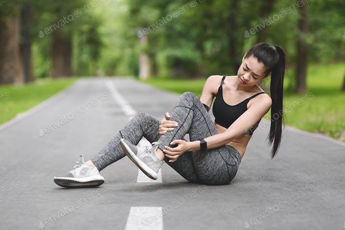 Sportverletzung. Asiatische Mädchen leiden unter Knöchelschmerzen Nach Joggen In Park