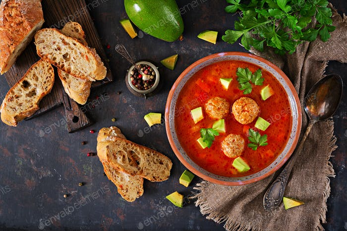 Spicy tomato soup with meatballs and vegetables. Served with avocado and parsley.