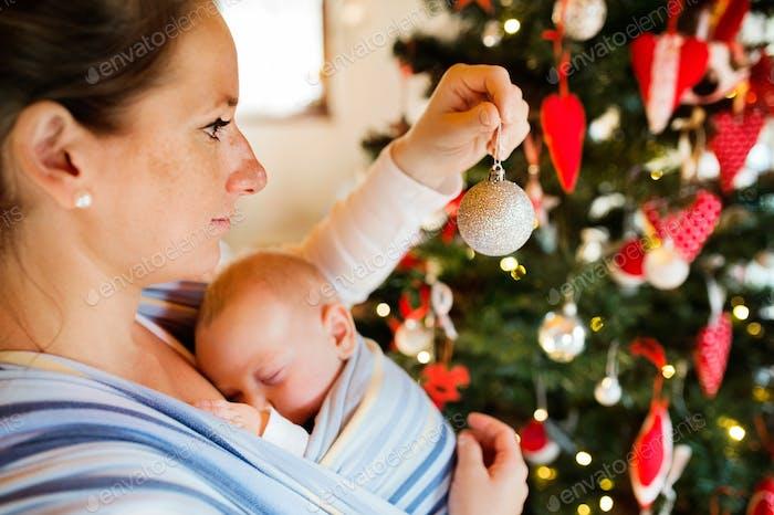 Junge Frau mit einem Baby dekoriert Weihnachtsbaum.