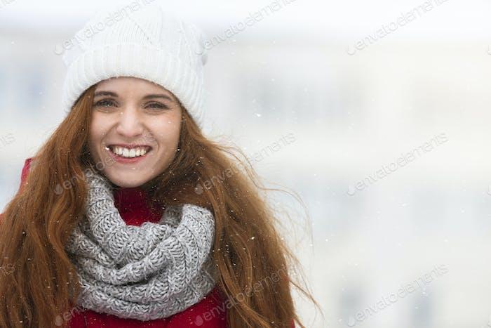 Beautiful girl enjoying first snow in city
