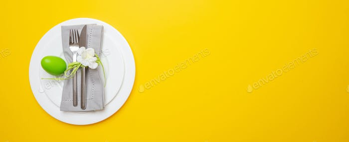 Easter eggs, green color painted in a white plate, yellow background, banner