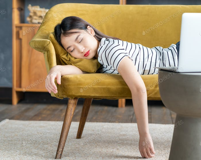 Young Asian girl fell asleep oncouch in front oflaptop. Cute woman is bored, tired or overworked