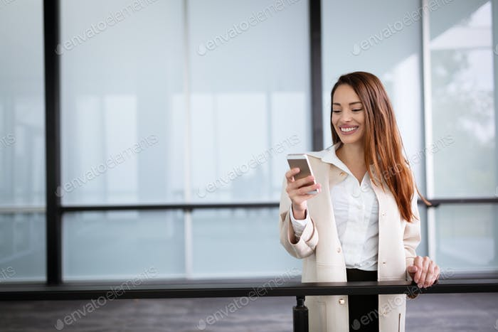 Businesswoman smiling and using phone