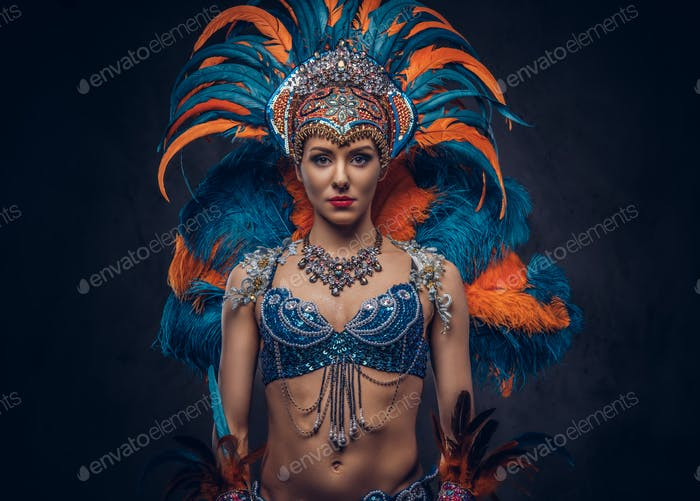 Portrait of a female in a colorful sumptuous carnival feather suit. Isolated on a dark background.