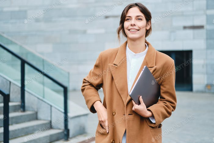 Young pretty smiling businesswoman in coat with laptop happily looking away outdoor
