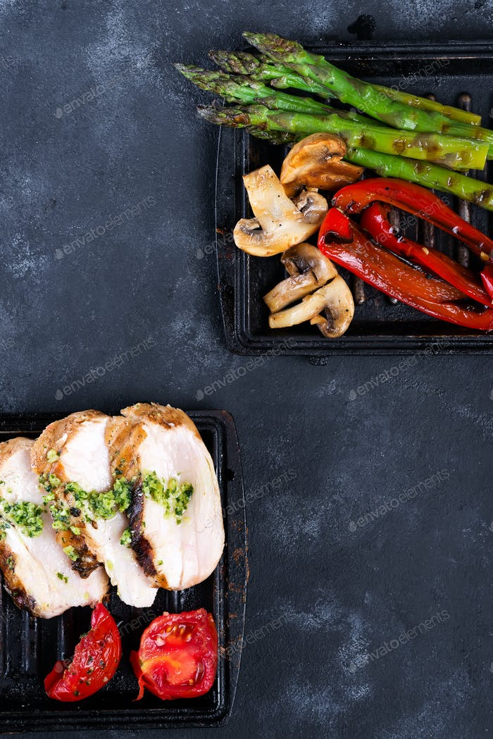Chicken breast grill with bbq vegetables and pesto sauce in a cast iron pan on a concrete background