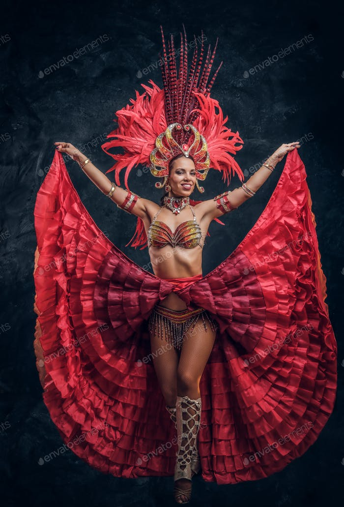 Beautiful brazil dancer in red feather costume is dancing on small scene