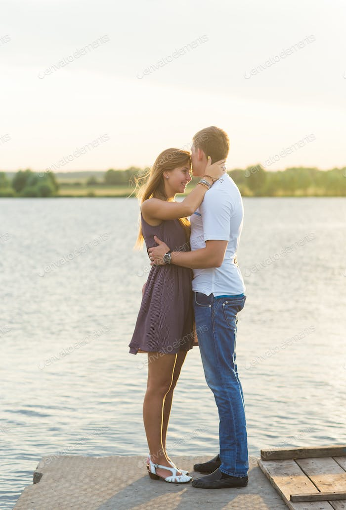 Young couple in love outdoors embracing and laughing together at lake