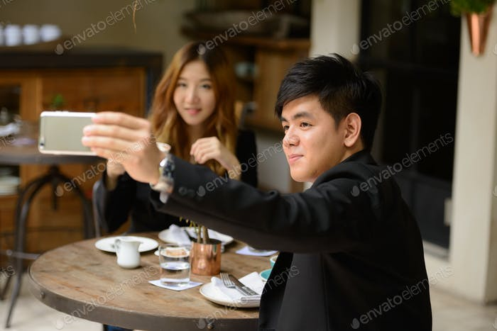 Young Asian business couple taking selfie together at the coffee shop