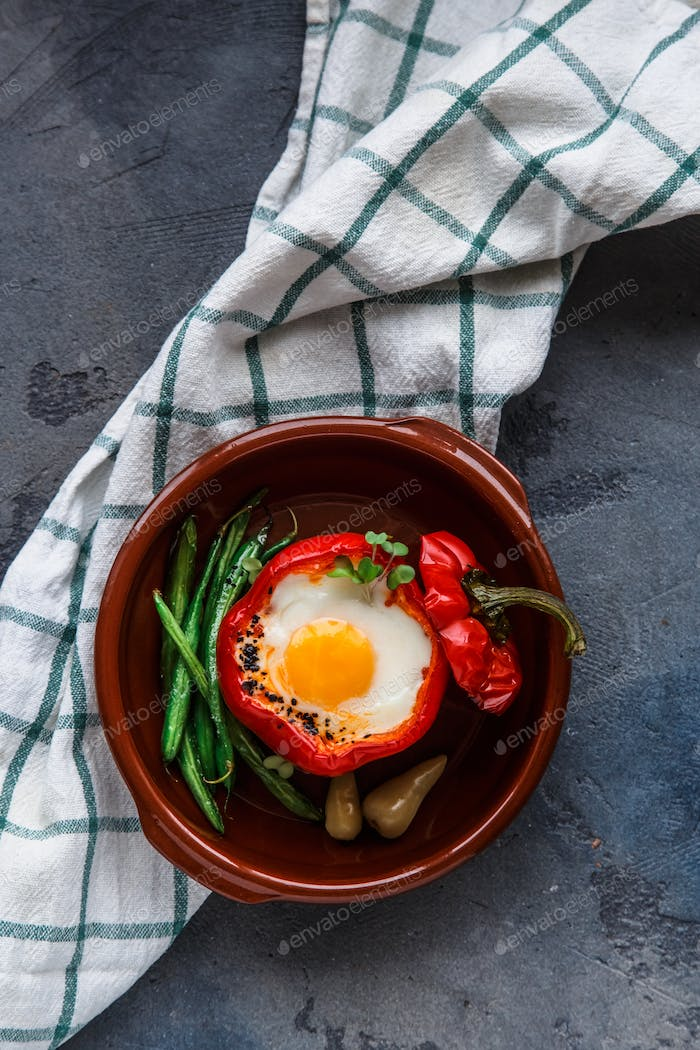 Healthy breakfast with egg baked in bell pepper with green beans