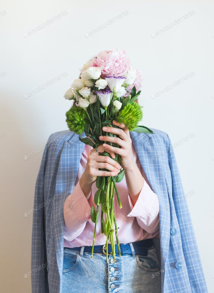 Woman in blue jacket holding pastel peony bouquet
