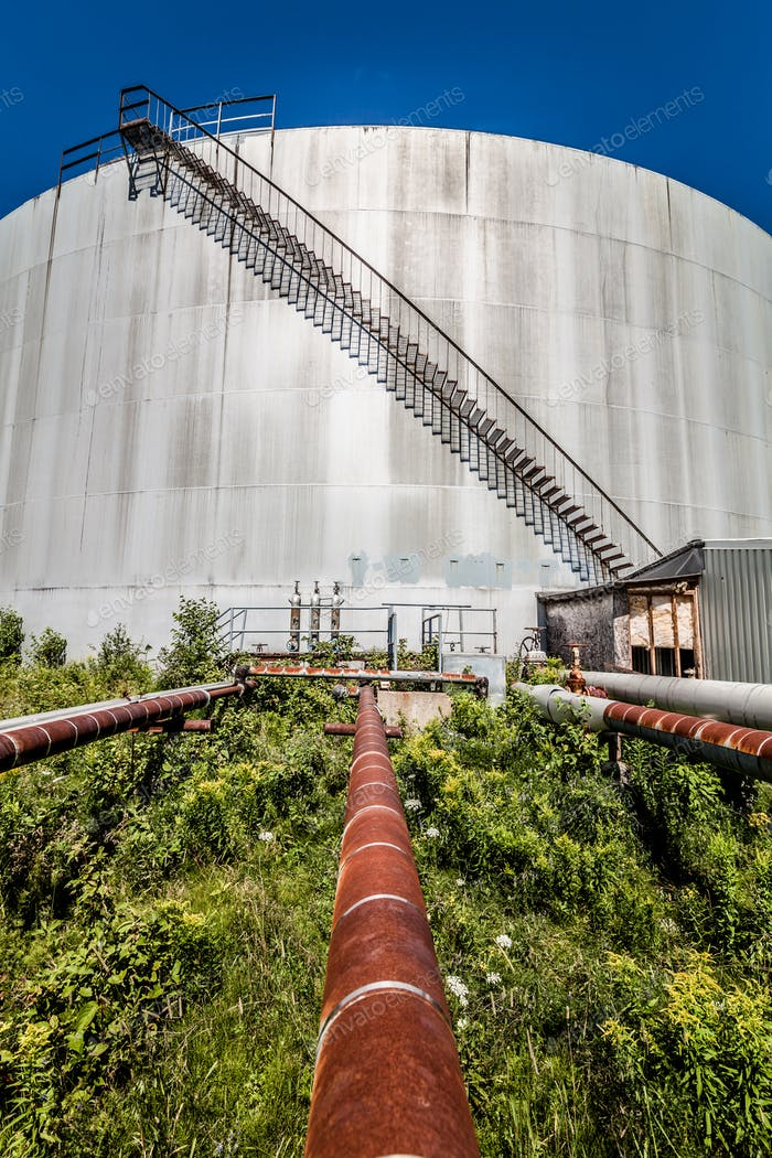 Abandoned Oil Refinery Gas Tank and Rusty Pipeline