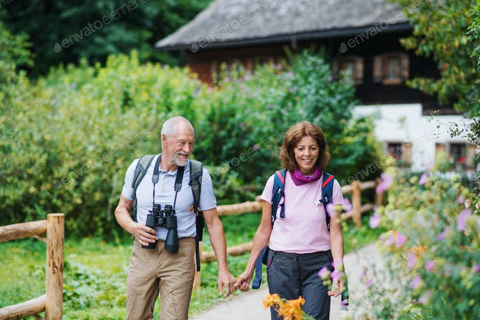 A senior pensioner couple with binoculars hiking,holding hands.