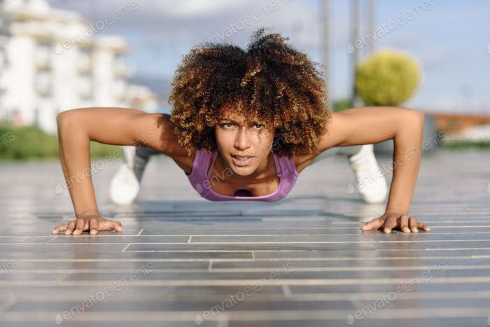 Black fit woman doing pushups on urban floor.