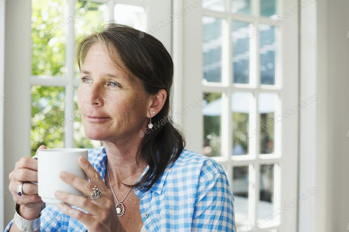 A woman having a cup of coffee.