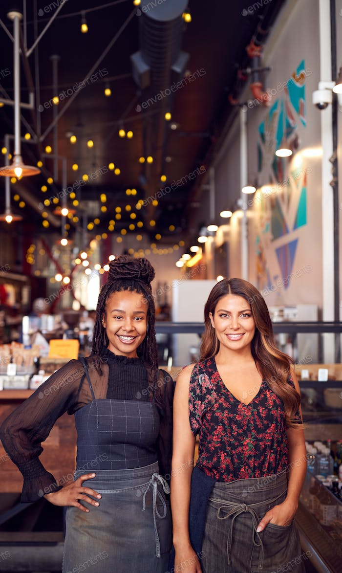Portrait Of Two Female Coffee Shop Owners Standing At Sales Desk