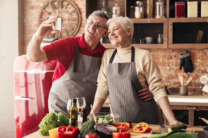 Senior paar nehmen selfie auf Handy in Küche