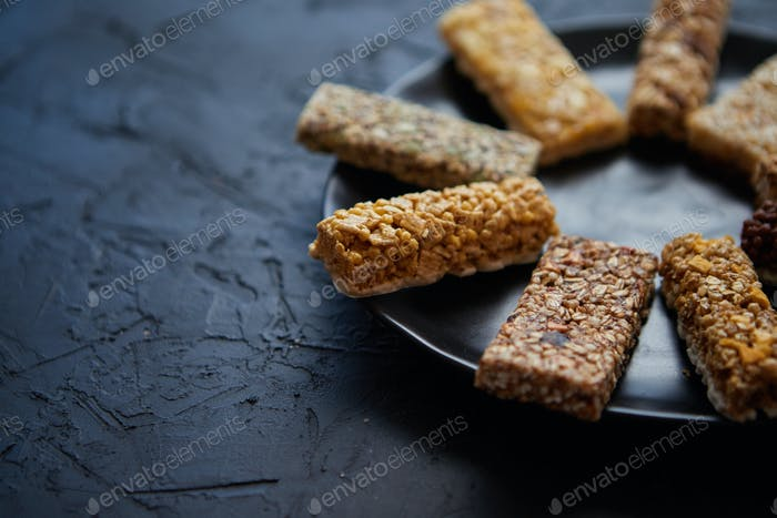 Different kind of granola fitness bars placed on black ceramic plate on a table