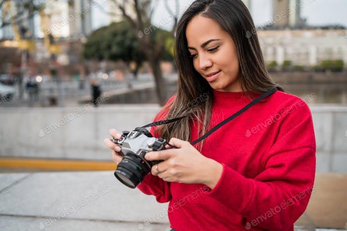 Молодая женщина использует профессиональную камеру.