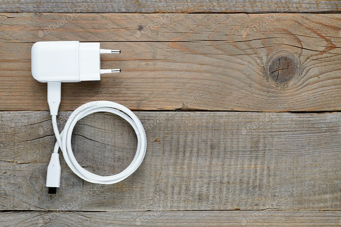 Charger for tablet or smartphone on wooden table top view