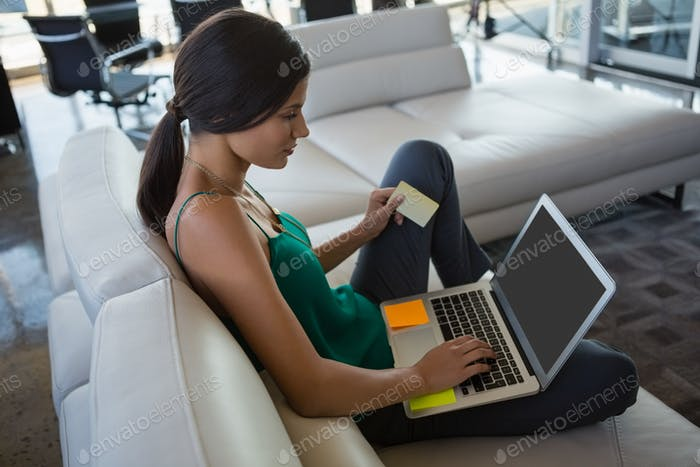 Woman using laptop while relaxing on sofa at office